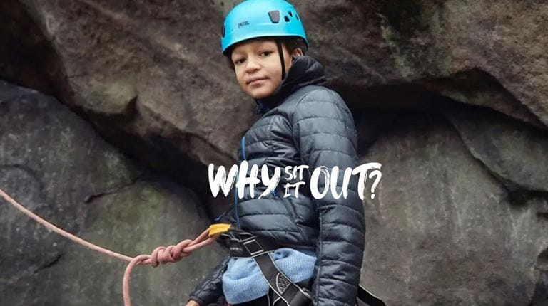 A boy with blue safety helmet and safety rope climbs a rock face