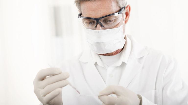 Male researcher taking a sample wearing goggles, face mask and gloves